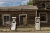 Old Gas Pumps in Front of Derelict Buildings Fotografie-Druck von Ami Vitale