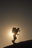 A Hiker Traverses a Ridge with Walking Poles Fotografisk trykk av Macduff Everton