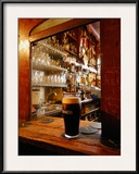 A Pint of Dark Beer Sits in a Pub Service Window Framed Photographic Print by Jim Richardson