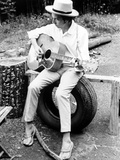 Bob Dylan Seated on Wheel Playing Guitar wearing White Long Sleeves and Slippers Foto af  Movie Star News