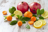 Oranges, Limes, Lemons, Clementines and Pomegranates on White Wooden Table Lámina fotográfica por Jana Ihle