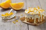 Small Orange Cake with White Icing on Wooden Table Valokuvavedos tekijänä Jana Ihle