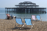 Deckchairs on the Pebble Beach Seafront with the Ruins of West Pier Brighton England Foto von Natalie Tepper