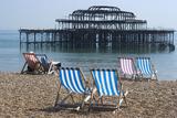 Deckchairs on the Pebble Beach Seafront with the Ruins of West Pier Brighton England Fotografía por Natalie Tepper
