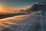 Snow Blows across an Icelandic Road at Sunrise with Mountains Looming in the Distance Stampa fotografica di Alex Saberi