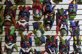 Colorful Carved Wooden Masks Hang for Sale on a Wall in a Tourist Shop in Costa Rica Reproduction photographique par Jonathan Kingston
