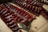Strips of Smoked Salmon are Cut Up for Canning, in a Cabin at a Denai'Ina Fish Camp Reproduction photographique par Beth Wald
