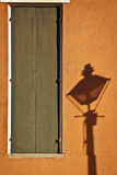 A Streetlight Casts a Shadow Near a Door on a Bright Orange Wall Stretched Canvas Print by Eduardo Rubiano