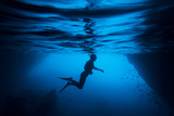 Silhouette of a Swimmer Snorkeling Near a Cave on Santiago Island in the Galapagos Fotografie-Druck von Jeff Mauritzen